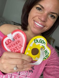 Woman holding hearts from a corporate team-building event.
